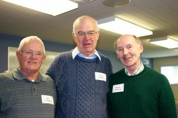 Three gentlemen post for a picture at the Retiree Luncheon