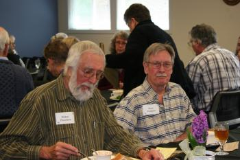 Two gentlemen seated at a table at the Retiree Luncheon