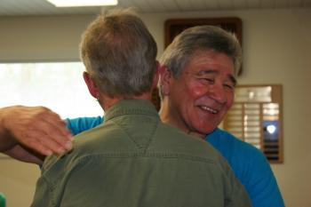 Two men share an embrace at the Retiree Luncheon